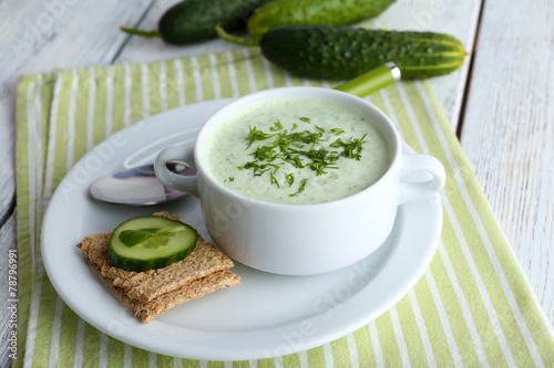 canvas print picture Cucumber soup in bowl on color wooden table background