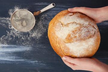 Loaf of freshly bread in female hands