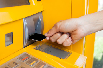 inserts a plastic card into the ATM
