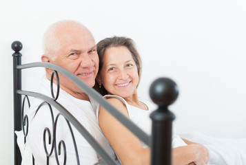 elderly couple embracing in bed.
