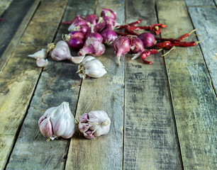 Close up garlic,onions and dry pepper on wooden table background