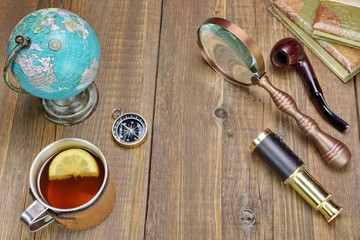 Tea Mag On Grunge Wood Table With Many Travel Objects