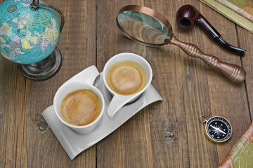 Two Coffee Cups And Adventure Objects On The Wooden Table
