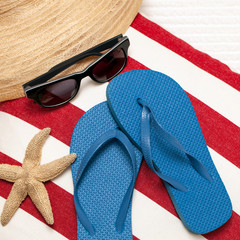 Flip flops, hat, towel, sunglasses and starfish for a day at the