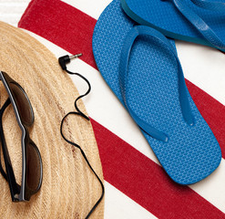 Flip flops, hat, towel, sunglasses and earphones for a day at th