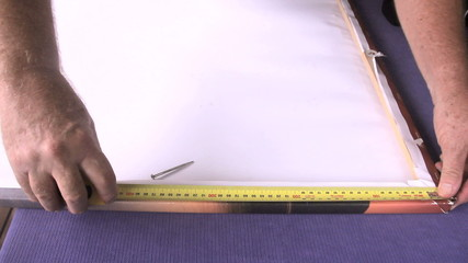 Measuring and marking a hole for a screw for a picture frame.