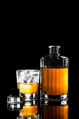 A glass of of Whiskey on the rocks against dark background