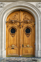 Beautiful old wooden door in Paris, France. Lion heads and other