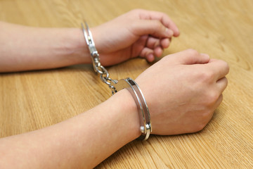 business hand arrested with handcuffs on the wooden table
