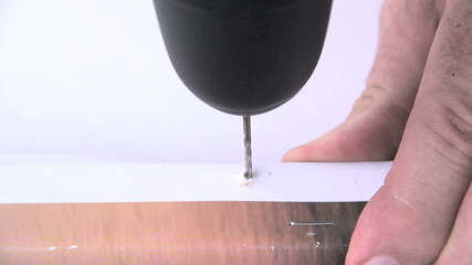 Drilling a marked hole for a screw to hang a picture frame.