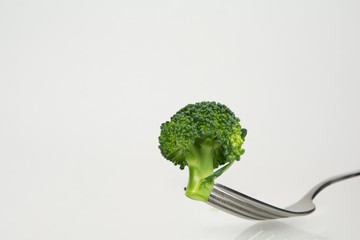 Fresh green broccoli on fork isolated on white