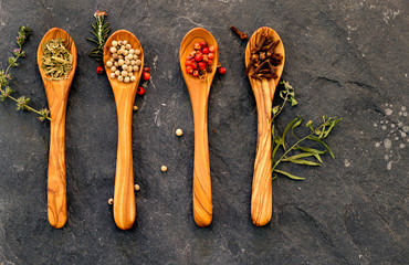 Spices and herbs in olivewood spoons on a dark gray stone backgr
