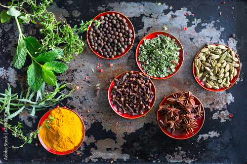 Fresh herbs and whole spices displayed on an old metal cooking s - 78805161