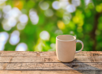 White coffee cup on wooden table at morning sunlight and bokeh b