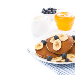 pancakes with banana, honey, blueberries and yogurt, isolated