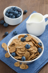 wholegrain flakes with blueberries and milk, vertical, top view