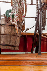 Wooden bucket, rope and nautical hardware on a sailboat deck. Cl