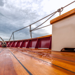 Wood deck of a sailboat at sea under stormy skies. Square format