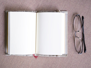 Blank book open with eyeglasses on table Top view