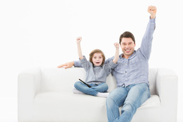 Father and his young son smiling on a couch
