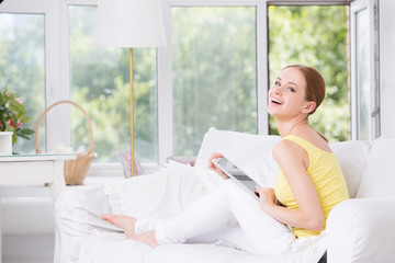 Young beautiful girl sitting on the couch and shows touchpad