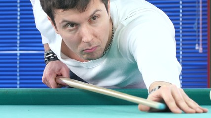 Guy takes aim, to make an impact on a billiard ball