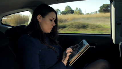 Beautiful business woman in taxi working with tablet