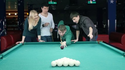 Young man doing kick on a billiard ball. Slow motion