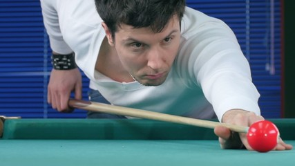 Guy takes aim, to make an impact on a billiard ball. Slow motion