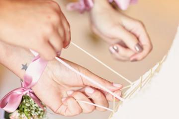 Brides maid helps bride dress in wedding dress for wedding day