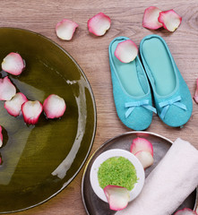 Spa bowl with water, rose petals, towel and slippers