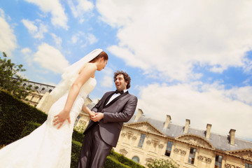 Bride and groom on a blue sky in Paris, France