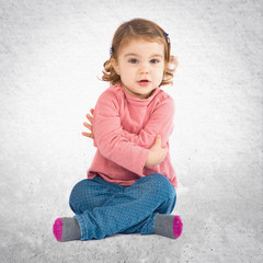 Little girl sitting over isolated white background