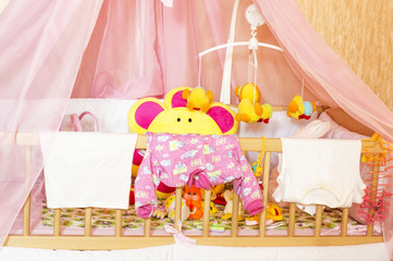 Different children's clothes and toys in the cot