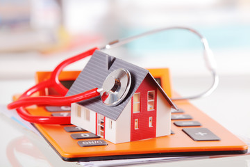 Model House with Stethoscope on Calculator Device