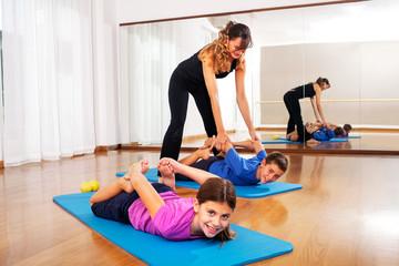 teacher explaining young boys fitness exercises to balance