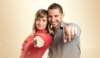 Couple pointing to the front over white background
