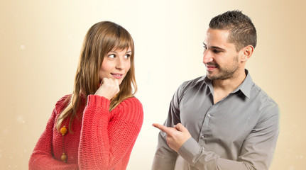Man pointing his girlfriend over white background