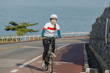 The girl cycling uphill on the  road.