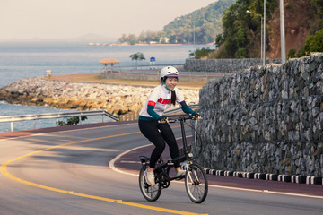 The girl cycling uphill on the road