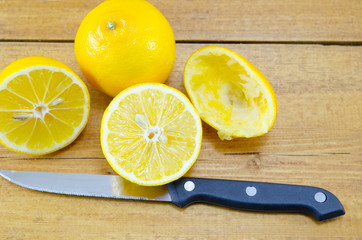 Halved and squeezed lemons and a knife