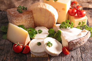 collection of cheese on wood background