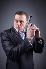 man in a business suit with a gun