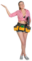 Woman in tool belt, with laptop under her armpit, showing empty