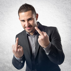 Young businessman doing the horn sign over white background