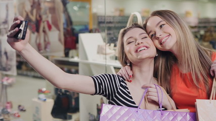 Two happy friends is taking selfie while shopping in mall.