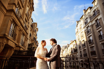 Bride and groom holding hands in Paris sorrounded by buildings