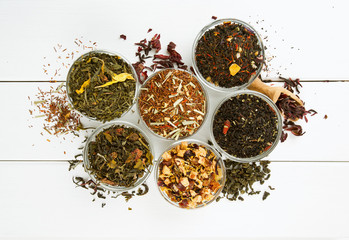assortment of dry tea in glass bowls on wooden surface