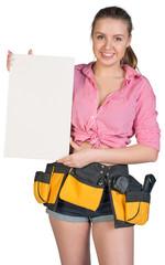 Woman in tool belt holding ceramic tile