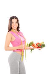 Woman holding a plate full of vegetables